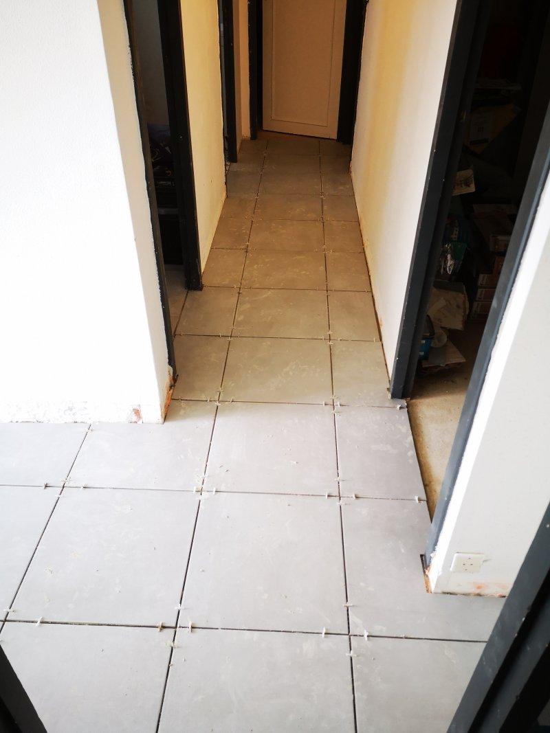 Pose de carrelage dans un couloir
