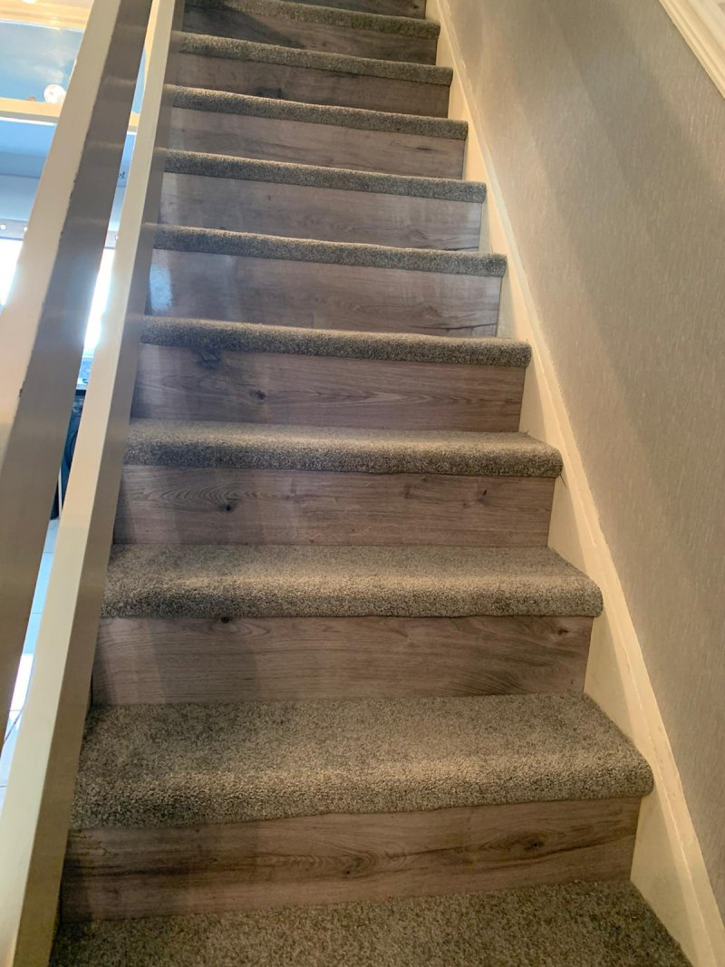 Stair carpet tread with laminate footing rise